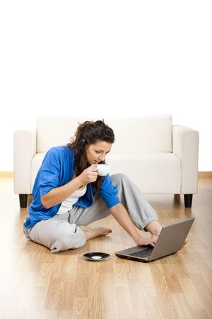 Portrait of a girl seated on floor and using laptop with a cup of coffee Stock Photo - 5186563
