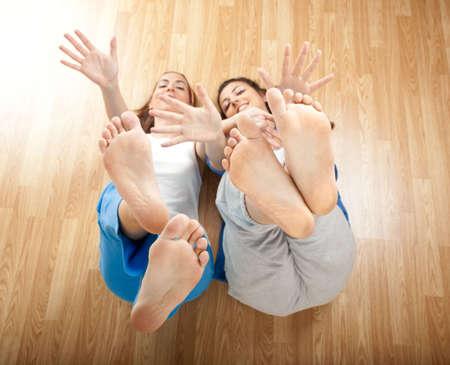 pied jeune fille: Deux belles jeunes femmes en s'amusant et en mouvement des mains et des pieds Banque d'images