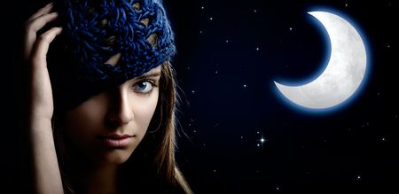 Portrait of a beautiful and young woman at night with a artifical moon on the background photo