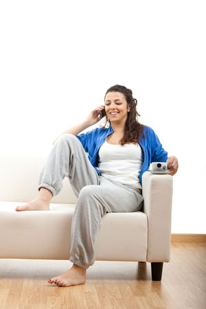 Portrait of a girl seated on the couch and making a phone call Stock Photo - 5276183