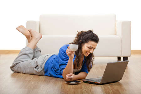 Portrait of a girl lying on floor and using laptop with a cup of coffee photo