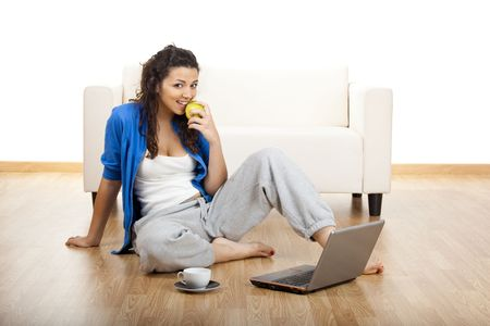 Portrait of a girl eating an apple and seated on floor with a laptop Stock Photo - 5276051
