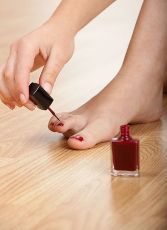 Woman applying red nail polish isolated on herself photo