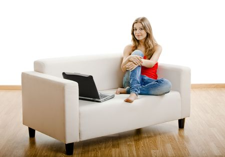 Beautiful young woman sitting on a sofa and working on a laptop Stock Photo - 5429343