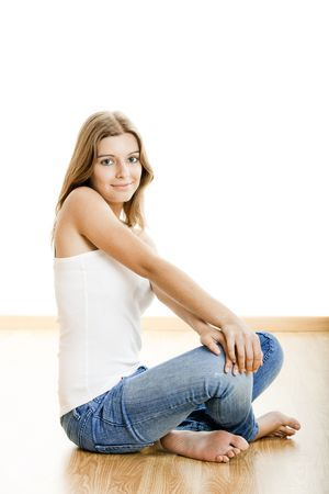 Portrait of a sexy young woman sitting on floor isolated over white background photo