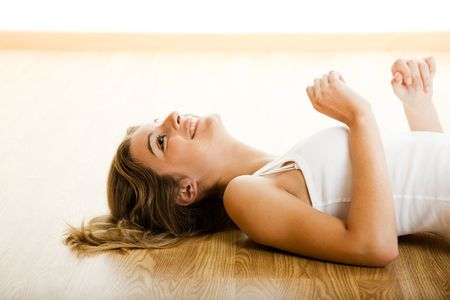Beautiful young woman lying on floor and smiling photo