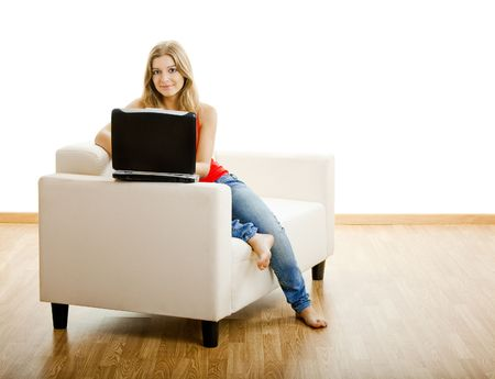 Beautiful young woman sitting on a sofa and working on a laptop Stock Photo - 5429325