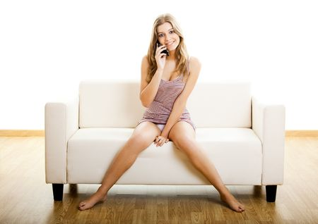 Beautiful young woman sitting on a couch and making a phone call photo