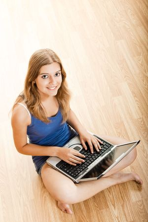 Beautiful young woman sitting on floor and working on a laptop Stock Photo - 5518061