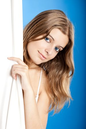 Beautiful young woman peeking behind a white sheet photo