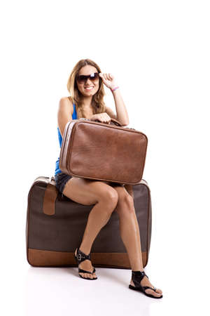 luggage travel: Beautiful young woman seated and waiting with two old leather suitcases, isolated on white Stock Photo