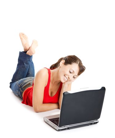 Beautiful and happy young woman lying on floor and working on a laptop photo