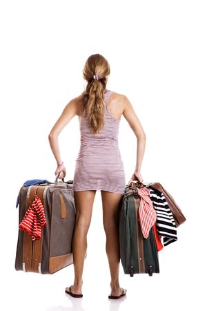 carying: Rear view of a beautiful and young woman carying the baggage with clothes