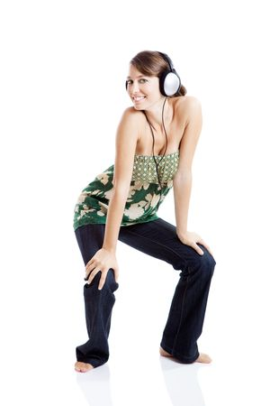 Beautiful young woman listen music and dancing with headphones, isolated on white photo