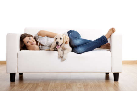 lying on couch: Young beautiful woman at home with her cute dog Stock Photo