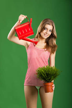 sexy teen: happy sexy female gardener over a green background