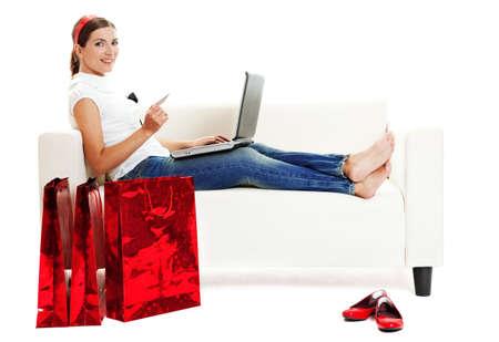 chicas comprando: Hermosa mujer joven haciendo tiendas en l�nea con una tarjeta de cr�dito, el concepto de consumo