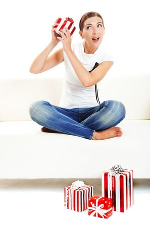 Young woman on a sofa opening the Christmas presents photo