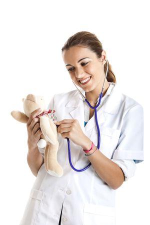 Beautiful female nurse taking care of a teddy bear with stethoscope photo