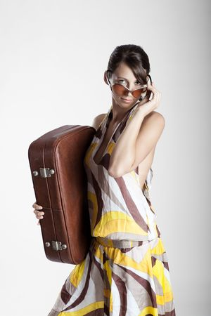 Beautiful fashion woman posing with a vintage suitcase photo