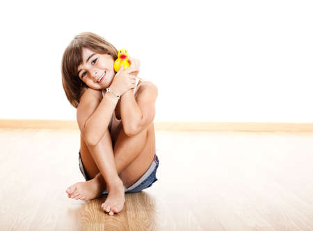 little girl sitting: Happy little child smilling and playing with a yellow rubber duck