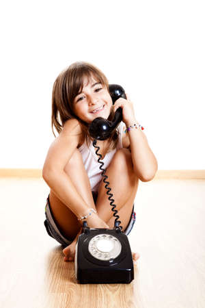 calling communication: Little child maling a phone call with a old vintage phone