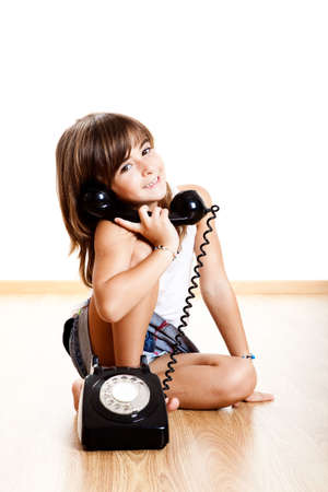 little girl sitting: Little child maling a phone call with a old vintage phone