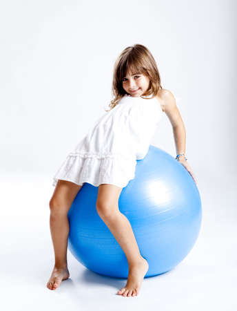 Happy little child playing with a big blue ball photo