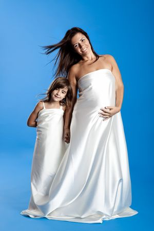 Beautiful pregnant woman with her little daughter isolated on a blue background  photo