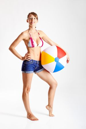 Beautiful young woman posing in bikini with a beach ball photo