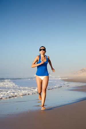 Beautiful young woman running on the beach Stock Photo - 6359276