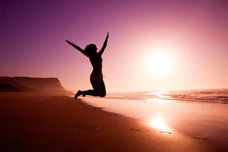 persona saltando: Foto de una silueta femenina de una ni�a saltando sobre la playa en la puesta de sol Foto de archivo