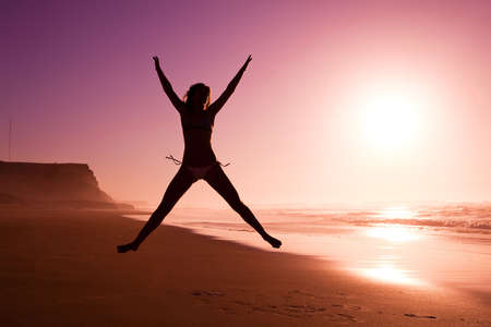 joy health: Picture of a female silhouette of a young girl jumping on the beach at the sunset Stock Photo