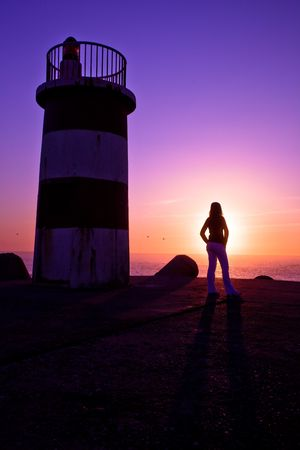 Beautiful landscape picture of a lighthouse and a woman looking the sunset photo