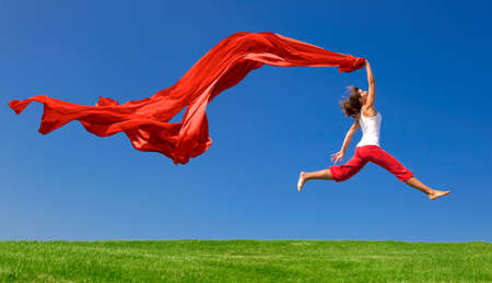 Beautiful young woman jumping on  a green meadow with a colored tissue photo