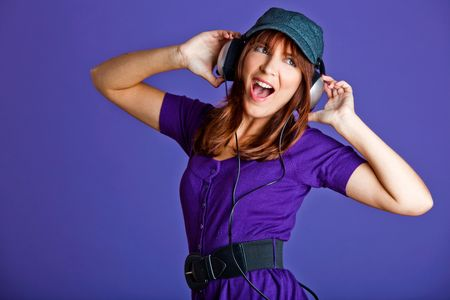 Beautiful and happy young woman listen music with headphones, over a violet background Stock Photo - 6534230