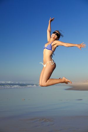 Beautiful young woman jumping on the beach photo