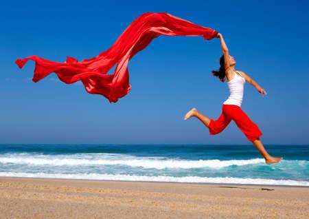 persona saltando: Hermosa mujer joven saltando sobre la playa con un tejido color Foto de archivo