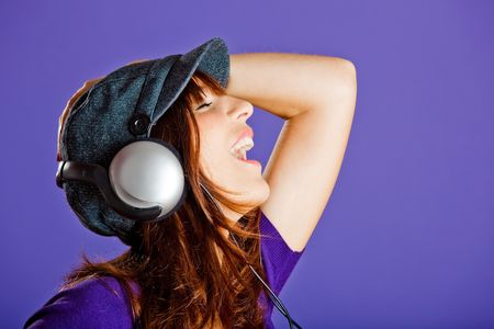 woman listening to music: Beautiful and happy young woman listen music with headphones, over a violet background