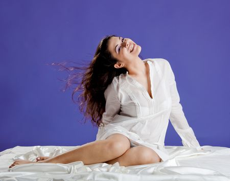 Beautiful and happy young woman smiling on the bed by the morning photo