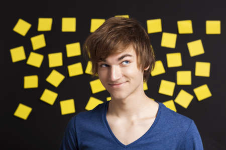 Happy student in front of a board with yellow notes and looking in to the camera photo