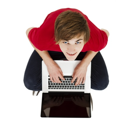 Top view of young man sitting in the floor and working with a laptop photo