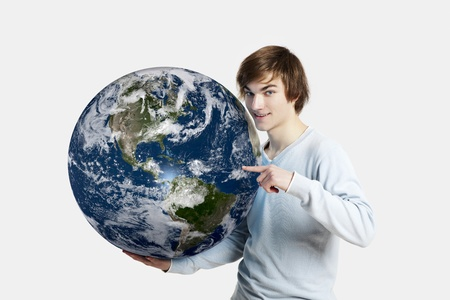 Handsome young man pointing and holding the planet earth on its hands,  isolated on white photo