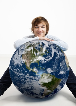 Young man resting over a small planet earth photo
