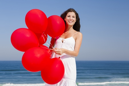hapiness: Beautiful girl with red ballons in the beach  Stock Photo