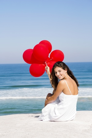 Beautiful girl with red ballons sitting in the beach Stock Photo - 21141210