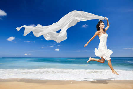 Beautiful woman running and jumping in the beach with a white tissue