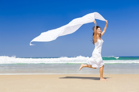 hapiness: Beautiful woman running and jumping in the beach with a white tissue