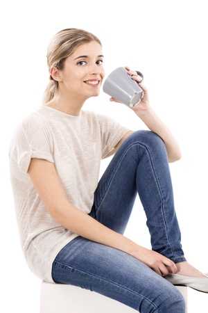 young woman sitting: Beautiful blonde girl sitting and drinking coffee, over a white background Stock Photo