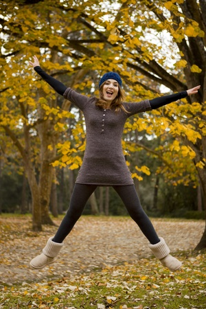Beautiful and happy woman jumping in a autumn day photo